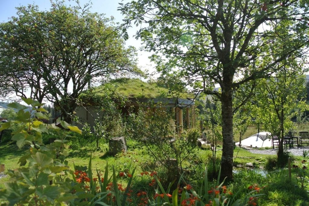 The straw bale roundhouse blending in nicely with nature at Ty Mam Mawr off grid eco retreat centre