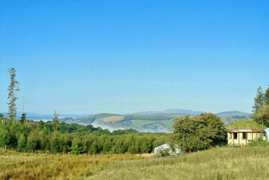 Ty mam mawr off grid eco retreat centre roundhouse and big yurt view west to snowdonia in summer
