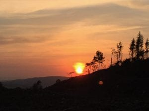 Fiery sunset off grid sustainable eco glampsite and glamping