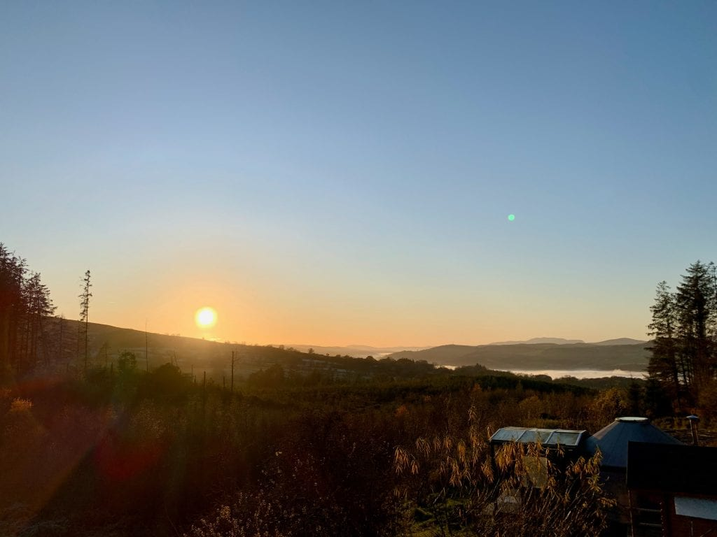 Sunset over the small yurt from the roundhouse roof off grid sustainable eco glampsite and glamping