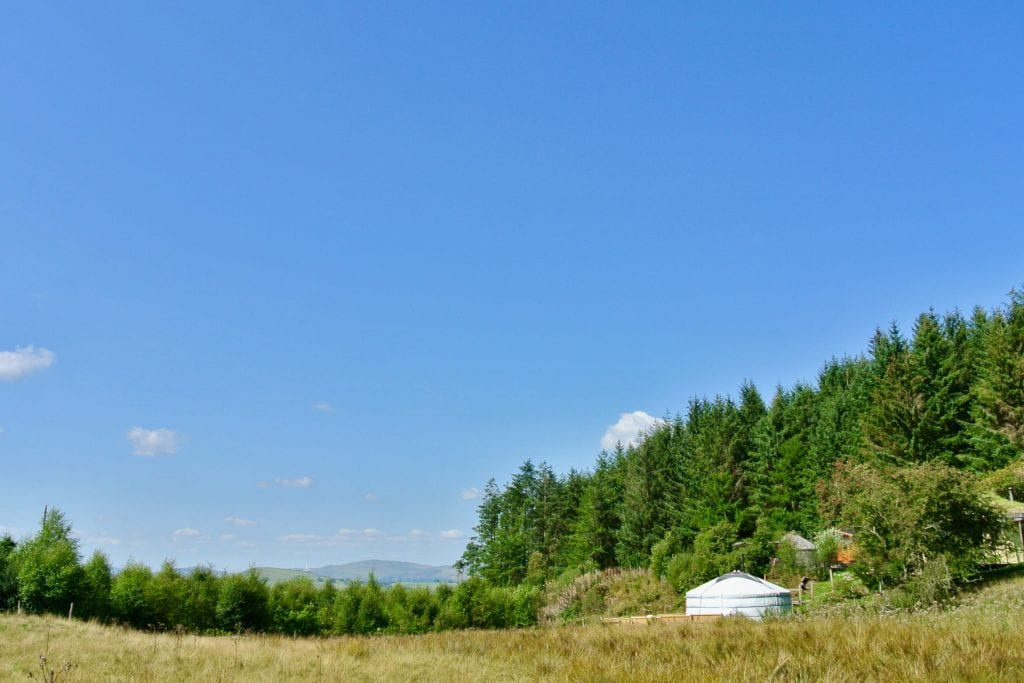Ty crwn mawr yurt a view from the field off grid sustainable eco glampsite and glamping
