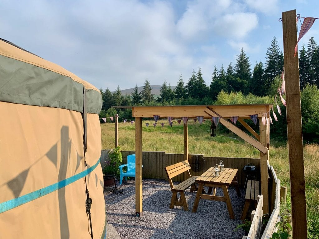 Ty crwn mawr yurt outside covered dining area and fire pit 1 off grid sustainable eco glampsite and glamping