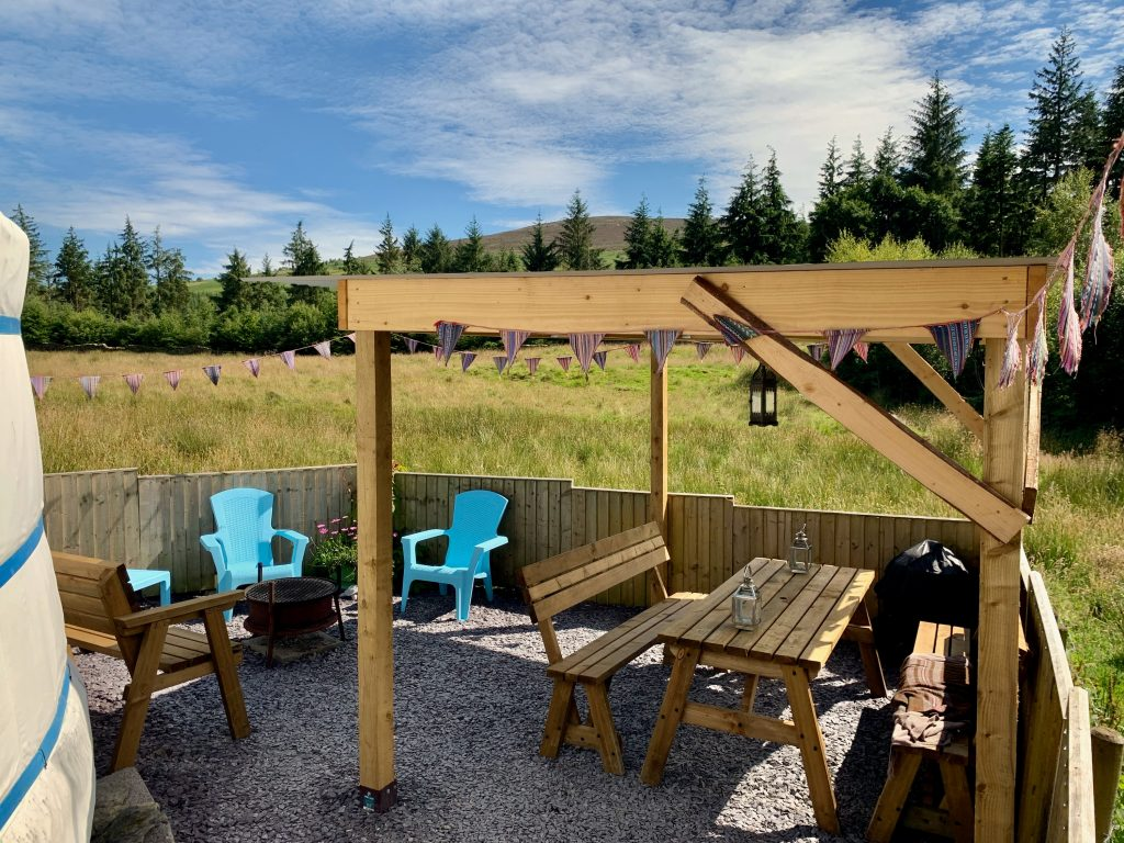 Ty crwn mawr yurt outside covered dining area and fire pit off grid sustainable eco glampsite and glamping