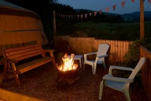 Ty crwn mawr yurt outside covered dining area and firepit nighttime and evening 10 off grid sustainable eco glampsite and glamping