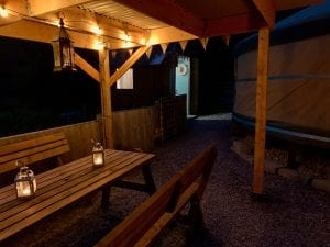 Ty crwn mawr yurt outside covered dining area and firepit nighttime and evening 11 off grid sustainable eco glampsite and glamping