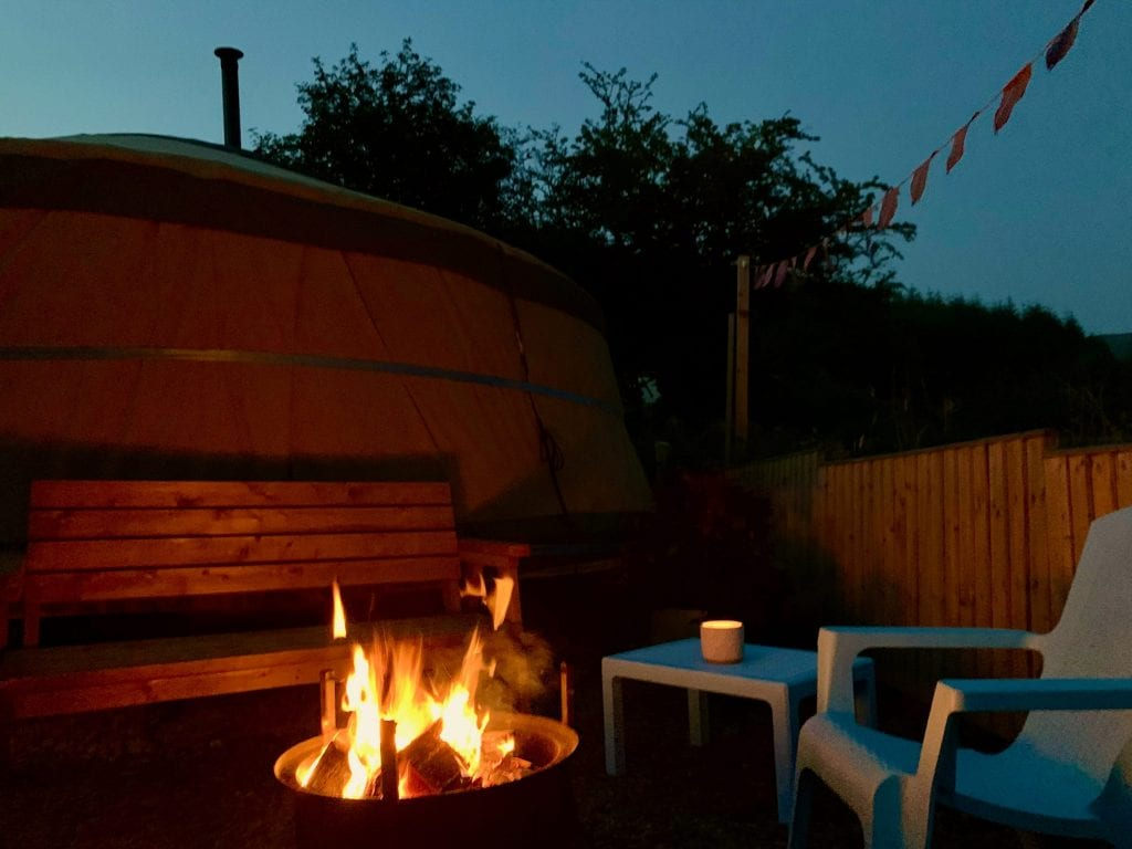 Ty crwn mawr yurt outside covered dining area and firepit nighttime and evening 13 off grid sustainable eco glampsite and glamping