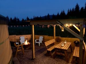 Ty crwn mawr yurt outside covered dining area and firepit nighttime and evening 14 off grid sustainable eco glampsite and glamping