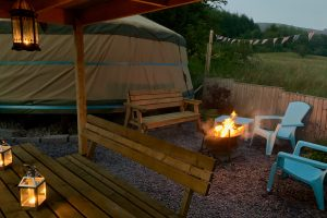 Ty crwn mawr yurt outside covered dining area and firepit nighttime and evening 2 off grid sustainable eco glampsite and glamping