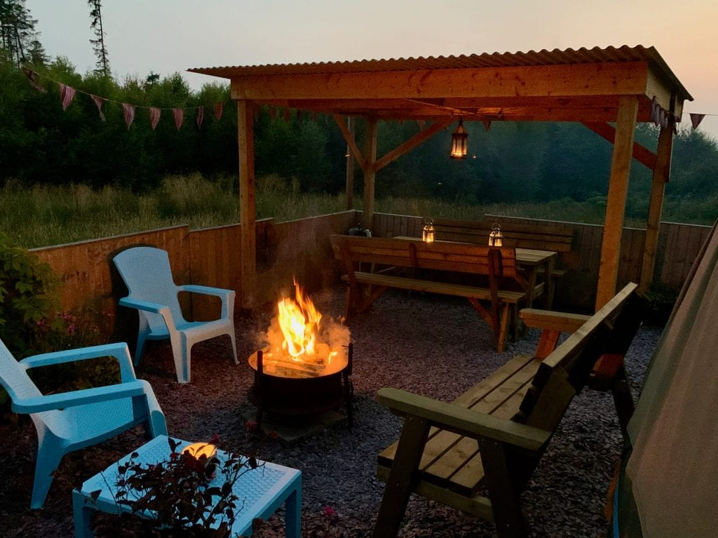 Ty crwn mawr yurt outside covered dining area and firepit nighttime and evening 3 off grid sustainable eco glampsite and glamping