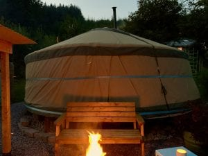 Ty crwn mawr yurt outside covered dining area and firepit nighttime and evening 5 off grid sustainable eco glampsite and glamping